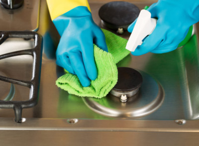 Closeup horizontal image of hands wearing rubber gloves while cleaning stove top range with spray bottle and microfiber rag